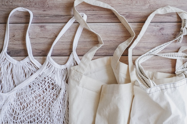 Eco tote cotton net shopping bag on wooden background. sustainability and reusable the source to save the environment.