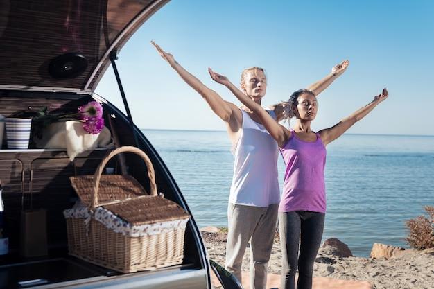 エコツーリズム。現代のトレーラーの近くで瞑想するエコツーリズムを楽しんで安心している旅行者のカップル