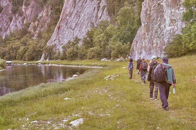 Экотуризм в горной местности, группа из пяти туристов идет по лесной тропе вдоль реки со скалистыми берегами.