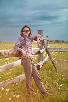 Эко-туризм на фермерском ранчо, прекрасная женщина отдыхает возле деревянного забора на пастбище для скота.
