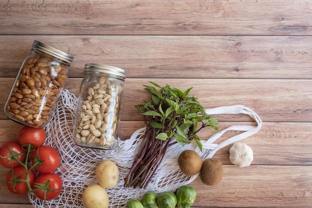 Сумка eco сетчатая здоровой еды vegan на деревянной поверхности. пластиковый бесплатный продуктовый магазин. вид сверху. плоская планировка