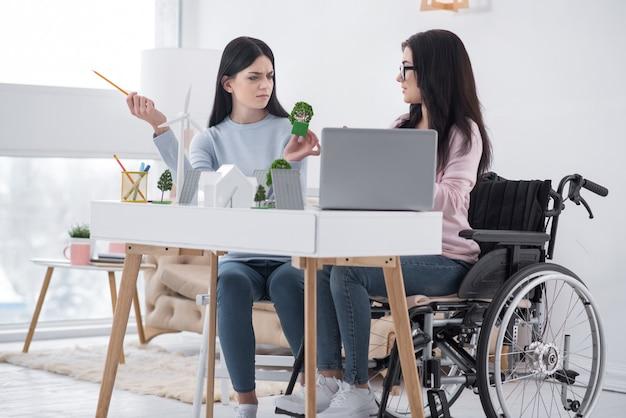 エコビレッジ。議論しながらテーブルでポーズをとる不安な不動の女性と同僚のローアングル