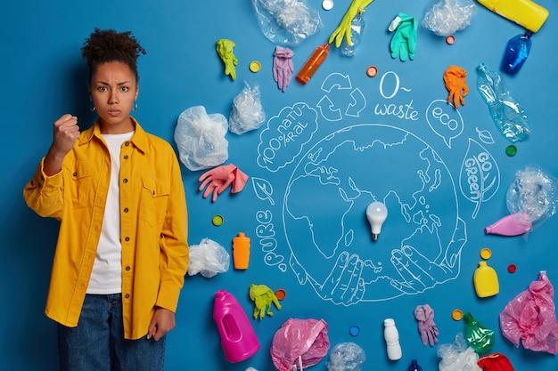 Eco volontario accanto al collage di rifiuti ambientali