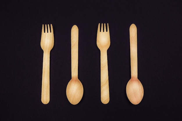 Eco wooden cutlery forks and spoons on a black background