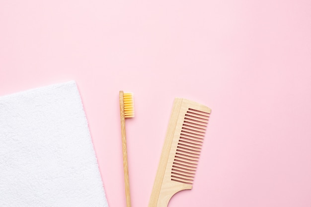Эко деревянная зубная щетка, расческа и белое банное полотенце на розовом