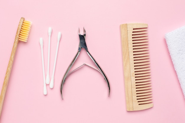 Eco wooden toothbrush, comb and nippers on pink