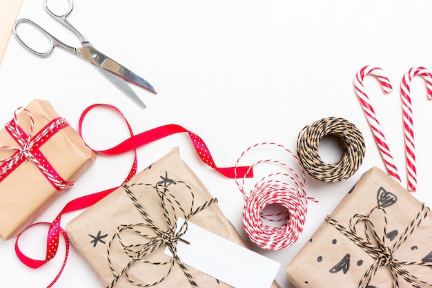 クリスマスとお正月のギフトのエコラッピング。ボックス、ストライプストリング、リボン、はさみ、ラベル、封筒、キャンディーロリポップ。テキストの場所