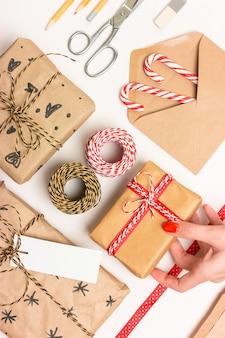 クリスマスプレゼントのエコラッピング。箱、縞模様のひも、リボン、はさみ、ラベル、封筒、キャンディケイン。アクセサリーレイアウト