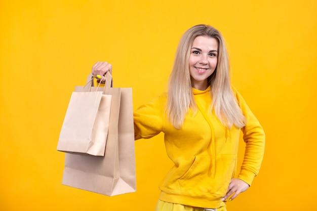 Портрет молодой довольно кавказской белокурой женщины с бумажными сумками eco в желтом спортивном костюме изолированном на желтой предпосылке,