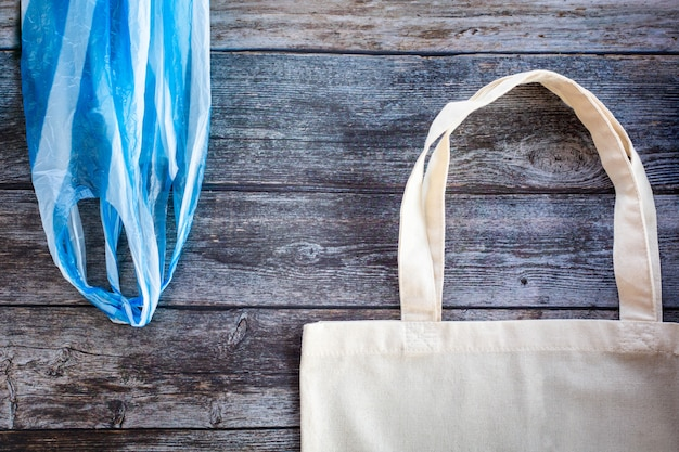 Хозяйственная сумка eco против полиэтиленового пакета на деревянной предпосылке, плоском положении. сохранить планету земля