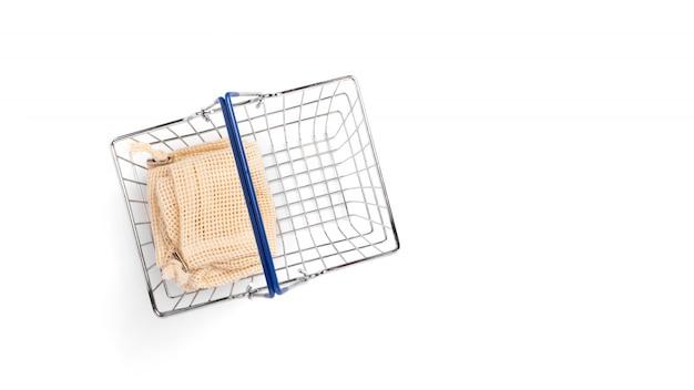 Сумки хлопка eco в корзине супермаркета металла на белой предпосылке с космосом экземпляра. изолированные. нулевая покупка продуктов питания. безотходная жизнь. экологический шоппинг. социально-экологическая ответственность