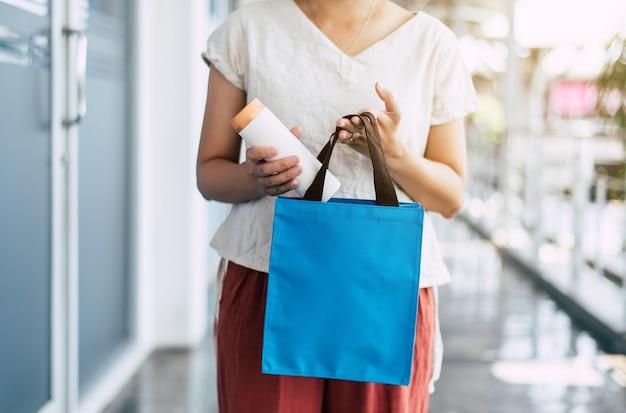 Женщина рук кладя бутылку питья многоразового использования в сумку eco