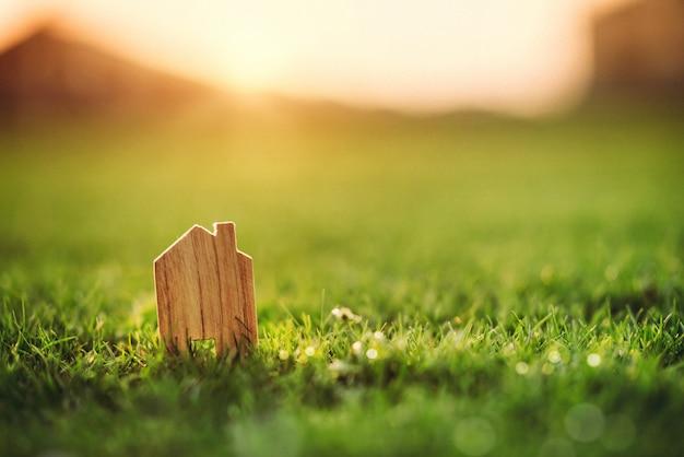 Концепция дома eco, маленькая модель дома над заходом солнца зеленой травы соперничающим.
