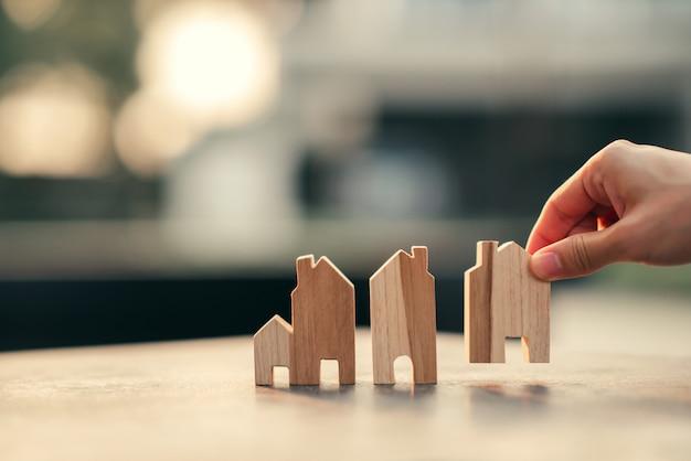 Рука женщины выбирая мини модель деревянного дома, планируя недвижимость покупки, концепцию значка дома eco.