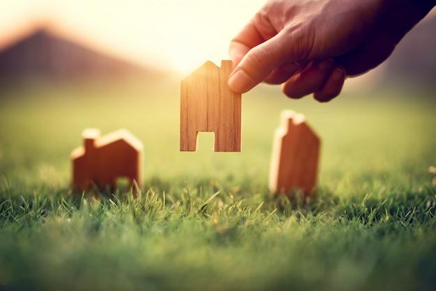 Рука женщины выбирая мини модель деревянного дома на зеленой траве, планируя недвижимость покупки, концепцию значка дома eco.