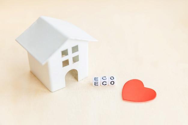 Миниатюрная игрушка модель дома с надписью eco буквы слова на деревянном фоне. эко деревня, абстрактный фон окружающей среды. экология безотходная социальная ответственность переработка концепции био дома