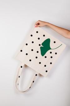 Экосумка из хлопчатобумажной ткани, макет, женская рука держит перевернутую белую экосумку с принтом на белом изол ...