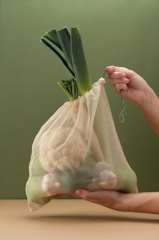 人間の手に新鮮な野菜が入ったエコバッグ