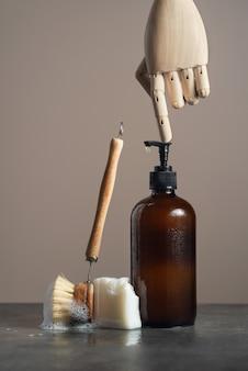 Экологичная янтарная стеклянная бутылка для мыла, деревянная щетка для посуды и мыло на темном мраморном фоне