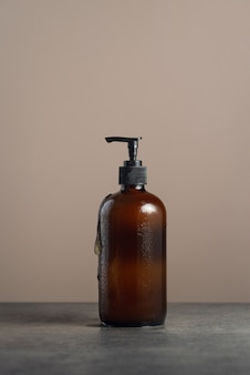 Ecofriendly amber glass soap dispencer with pump bottle filled with dishsoap or body wash on dark ma...