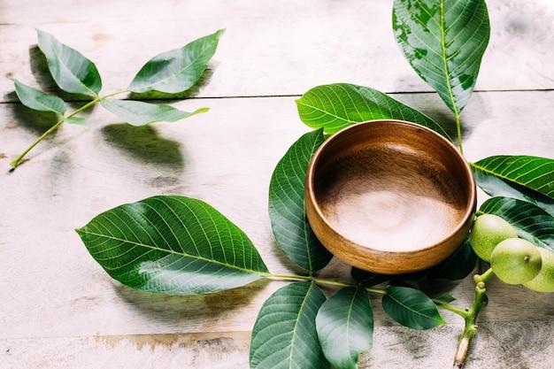環境に優しい背景緑の葉とテーブルの上の木製のボウル
