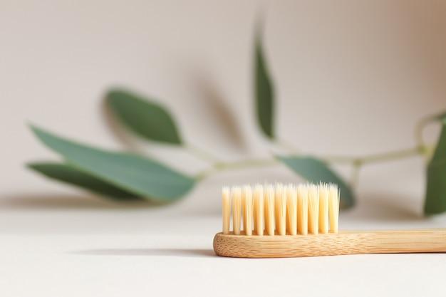 Экологичная бамбуковая зубная щетка на светло-бежевой текстуре крупным планом с листом на заднем плане