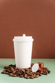 Ecofriendly disposable white paper cup with coffee beans and capsules, mock up design
