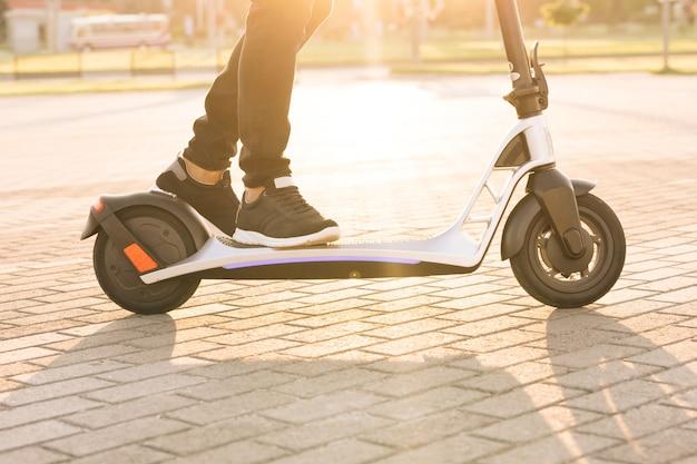 Экологичный транспорт, быстрая скорость вождения на электротранспорте, человек-хипстер, едущий на электрическом