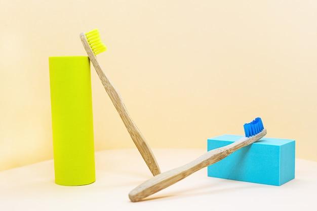 黄色の背景に自然な黄色と青の剛毛を持つ環境に優しい木製の歯ブラシ