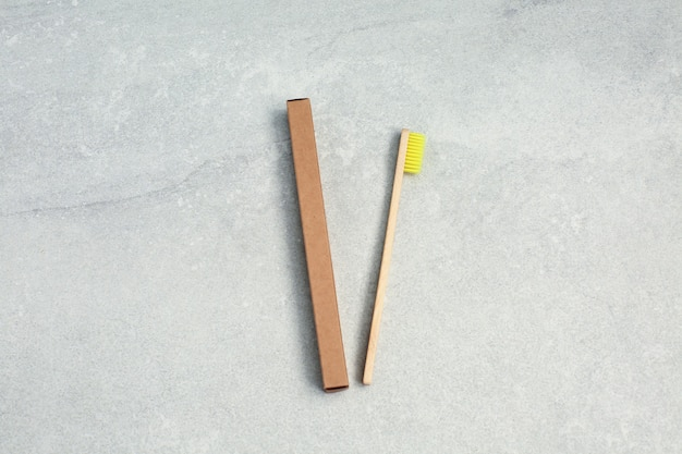 Ecological bamboo toothbrushe with yellow nylon bristles and brown paper box