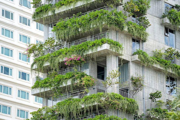 Ecological buildings facade with green plants and flowers on the stone wall of the facade of the house on the street of danang city in vietnam