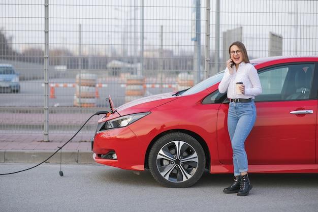 생태 자동차 연결 및 충전 배터리. 소녀는 스마트 폰을 사용하고 전원 공급 장치를 기다리는 동안 커피 음료를 사용합니다. 자동차의 배터리 충전을 위해 전기 자동차에 연결하십시오. 프리미엄 사진