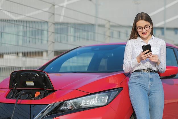 생태 자동차 연결 및 배터리 충전. 스마트 폰과 대기 전원 공급 장치를 사용하는 소녀는 자동차의 배터리를 충전하기 위해 전기 자동차에 연결