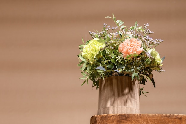 Экологическая композиция с букетом цветов в картонной вазе diy, стоящей на старом деревянном столе на бежевом цвете с тенями с копией пространства. низкий угол.