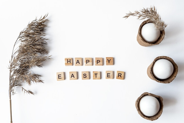 Ecological concept with easter white eggs with pampas grass and happy easter inscription.