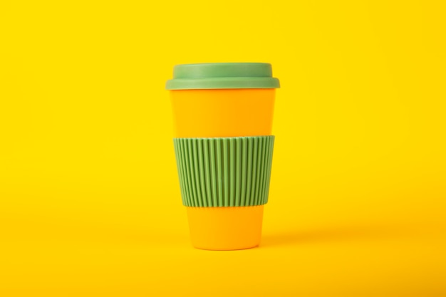 Ecological cup for coffee with green lid on the yellow surface