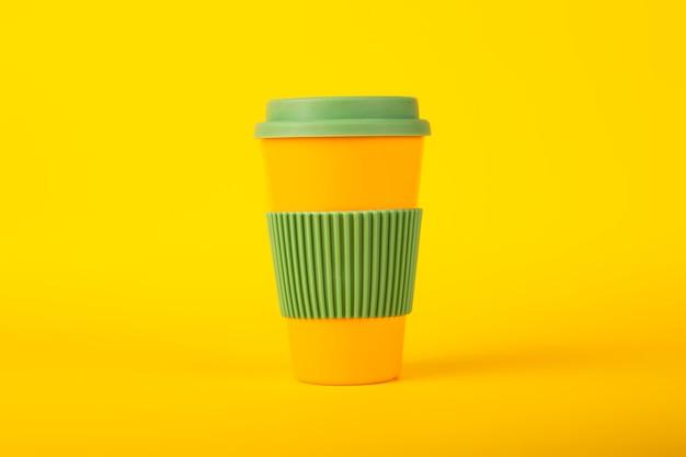 Экологическая чашка для кофе с зеленой крышкой на желтой поверхности