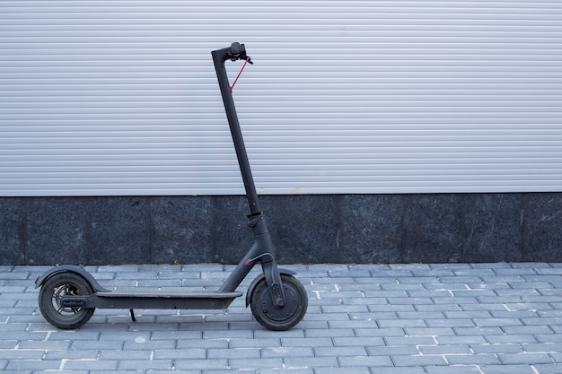 Ecological electrical transport, modern technology, electric scooter near grey wall