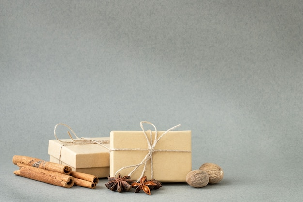 계피 스틱, 아니스 별 및 회색 배경에 메이스와 생태 선물 상자
