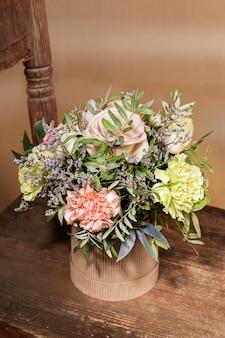 Экологическая праздничная композиция в стиле hygge с букетом цветов в картонной вазе diy, стоящей на старом деревянном стуле на бежевом фоне. вид сверху.