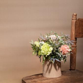 Экологическая праздничная композиция с букетом цветов в картонной вазе diy, стоящей на старом деревянном стуле на бежевом цвете с тенями и копией пространства.