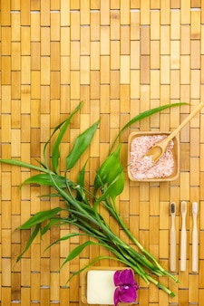 Ecological products concept with bath salt, bamboo leaves and  toothbrush on wooden mat