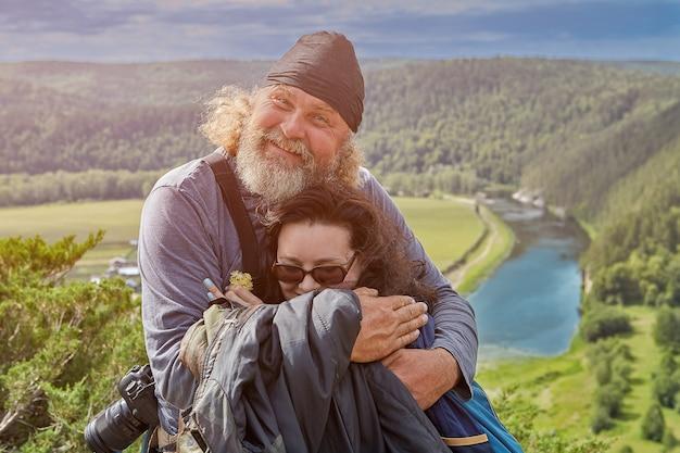 野生の高地でのエコツーリズム、父は針葉樹林と静かな川を背景に崖の上に娘を抱きしめます。