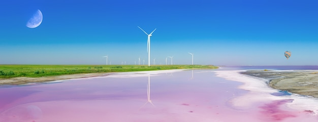 Ecologically windy power plants on the green shore of the pink lake