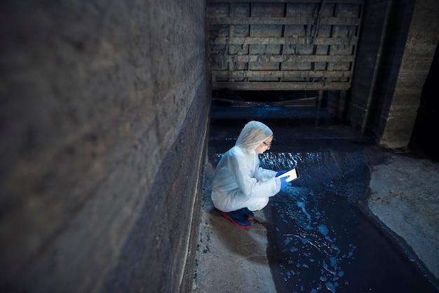 Эколог-эксперт отбирает пробы воды для изучения загрязнения и загрязнения сточных вод, выходящих из городских сточных вод в реку.