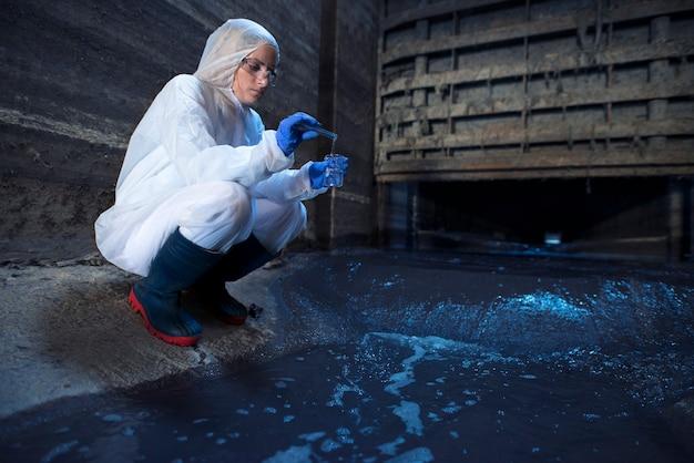 Эксперт-эколог берет пробы воды для изучения загрязнения и загрязнения сточных вод, выходящих из городских сточных вод в реку.