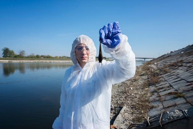 Эколог в белом защитном костюме держит мертвую рыбу, взятую из загрязненной реки.