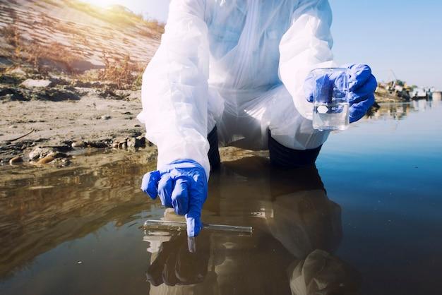 汚染と汚染のレベルを決定するために都市の川から試験管で水のサンプルを採取する生態学者