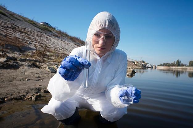検査のために試験管で川から水サンプルを採取する生態学者
