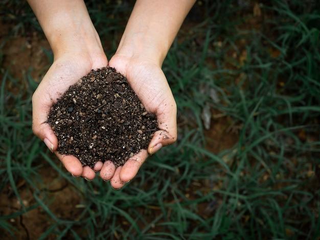 Понятие экологии. закройте вверх по женской руке, держащей органическую почву, полную естественного вещества, над фоном темно-зеленой травы с копией пространства.